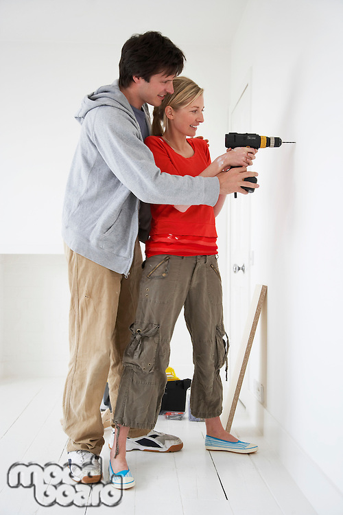 Couple drilling inside their new home