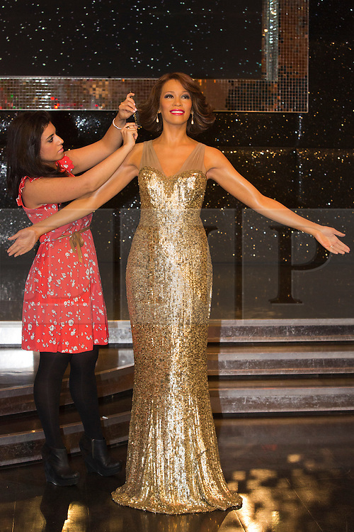 """© Licensed to London News Pictures. 21 October 2013. London, England. Pictured: hair sylist Caryn Bloom adds finishing touches. The 30-strong """"London Gospel Factory Choir"""" today welcomed the wax figure of singer Whitney Houston at Madame Tussauds London, where it will be on display until the middle of December 2013. Photo credit: Bettina Strenske/LNP"""