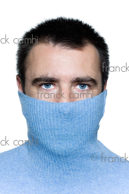 studio portrait on isolated background of anonymous shy man hiding behind his poloneck