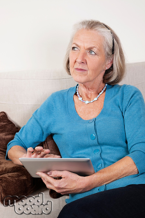 Thoughtful senior woman using digital tablet at home