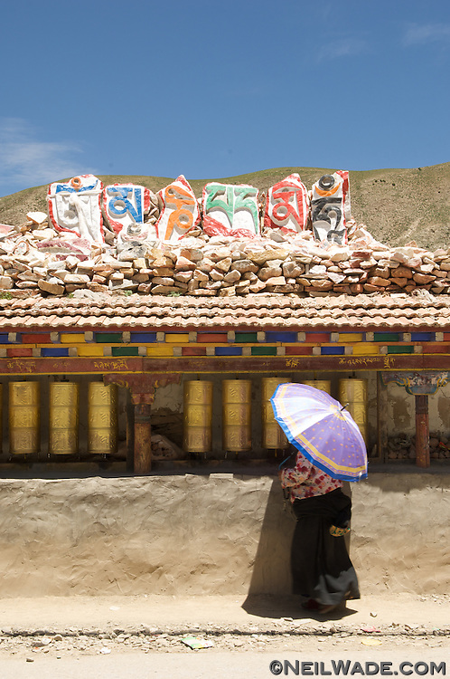 A traditionally dressed Tibetan Buddhist woman carries an umbrella as she spins prayer wheels at the giant Jiana (Gyanak) mani stone pile of Yushu, Tibet.