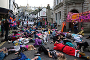 Activists from Extinction Rebellion perform a die in during an Eco action on New Years day on 1st January 2020 in St Ives, United Kingdom. Dressed in disco fancy dress, flares, afro's and general disco outfits the group danced through the streets of St Ives with their dance moves to Staying Alive making it a fun way to highlight the issues of climate change. They did a flash mob in the infamous local pub The Three Ferrets. The action lasted for two hours and they picked up new followers along the way. They also did Die Ins where they fall to the ground and lay for 2 minutes to highlight the plight of humanity because of the lack of action by governments around the world.