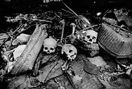 Human skulls and bones have been thrown on a pile of funereal refuse at a cemetery for the Bali Aga to make room for more recently deceased, descendents of the original Balinese, living inside the Batur caldera.  They do not bury their dead, but lay them out in bamboo cages to decompose under a sacred banyan tree, strangely without stench.  The cemetery, which is sandwiched between Lake Batur and the steep sides of the outer crater, is only accessible by dug out canoe from the village of Trunyan.  Bali, Indonesia.