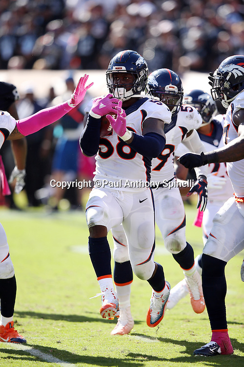 Denver Broncos outside linebacker Von Miller (58) runs with the ball as he celebrates after stripping Oakland Raiders quarterback Derek Carr (4) of the ball on a third quarter play that gives the Broncos the ball on the Raiders 16 yard line during the 2015 NFL week 5 regular season football game against the Oakland Raiders on Sunday, Oct. 11, 2015 in Oakland, Calif. The Broncos won the game 16-10. (©Paul Anthony Spinelli)
