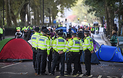 © Licensed to London News Pictures. 08/10/2019. London, UK. Large numbers of police watch over Extinction Rebellion activists near Parliament Square in Westminster. Activists have converged on Westminster for a second day, blockading roads in the area and calling on government departments to 'Tell the Truth' about what they are doing to tackle the Emergency. Photo credit: Ben Cawthra/LNP