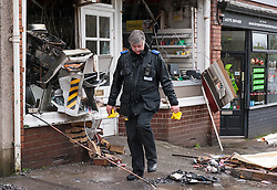 © Licensed to London News Pictures. 04/01/2016. Long Ashton, North Somerset, UK. A Police Forensics officer searches by a cashpoint and the front of the Post Office in Long Ashton near Bristol which has been destroyed in what is thought to have been a robbery using gas to blow up the cashpoint which happened about 3.30am today. Cash has been taken and three people have been arrested and are being held on suspicion of causing an explosion with intent to endanger life. There have been up to a dozen other similar attacks on cashpoints in the Bristol area in the last year or two. Photo credit : Simon Chapman/LNP