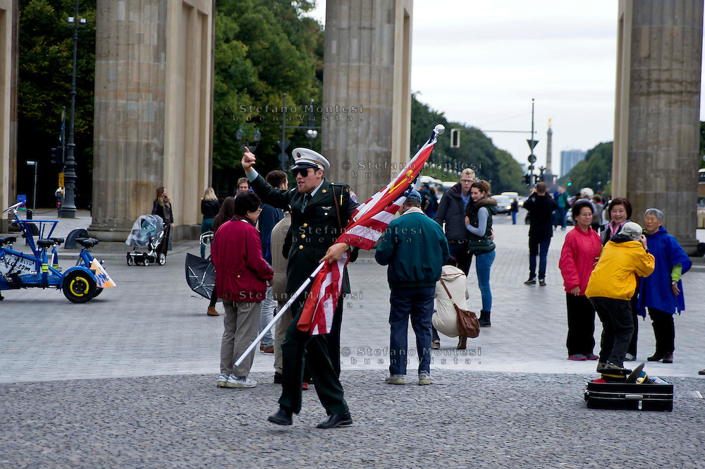 Berlino 16  Settembre 2013<br /> Attore che interpreta un militare dell'esercito degli Stati Uniti d'America  per farsi fotografare dai turisti  di fronte alla Porta di Brandeburgo<br /> Actor  playing a United States Army military policeman  pose for tourist photographs in front of the Brandenburg Gate, in the center of Berlin.