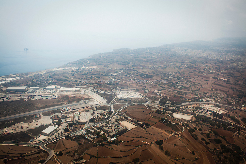 Malta - 21 August, 2012: Aerial view of the Hal Far Tent Village (center) and of the Hangar Site (bottom left) with respectively 100 and 34 containers where migrants live, in Hal Far, Malta,  on 21 August, 2012.<br /> <br /> The open centres in Malta serve as a temporary accomodation facility, but they ended becoming permanent accomodation centres, except for those immigrants who receive subsidiary protection or refugee status and that are sent to countries such as the United States, Germany, Poland, and others. All immigrants who enter in Malta illegally are detained. Upon arrival to Malta, irregular migrants and asylum seekers are sent to one of three dedicated immigration detention facilities. Once apprehended by the authorities, immigrants remain in detention even after they apply for refugee status. detention lasts as long as it takes for asylum claims to be determined. This usually takes months; asylum seekers often wait five to 10 months for their first interview with the Refugee Commissioner. Asylum seekers may be detained for up to 12 months: at this point, if their claim is still pending, they are released and transferred to an Open Center.<br /> <br /> Gianni Cipriano for The New York Times