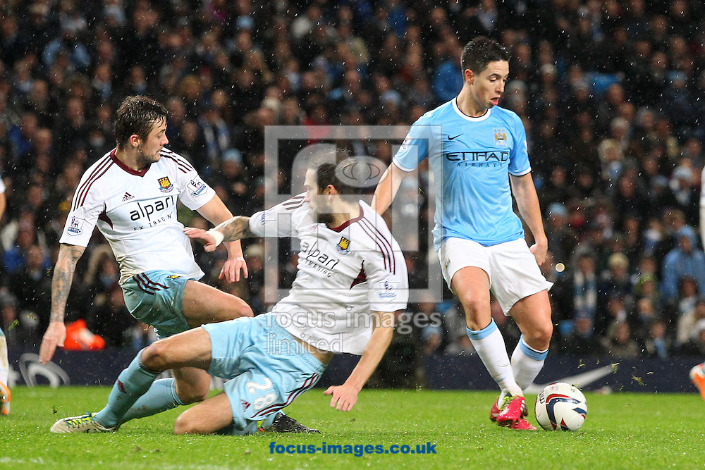 Picture by Paul Chesterton/Focus Images Ltd +44 7904 640267<br /> 08/01/2014<br /> Samir Nasri of Man City beats Roger Johnson of West Ham and George McCartney of West Ham easily  in action during the Capital One Cup Semi Final 1st Leg match at the Etihad Stadium, Manchester.