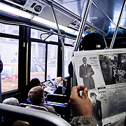 Man reading a newspaper in the bus