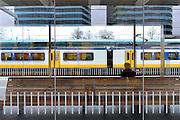 Nederland, Arnhem, 10-12-2015 Treinen staan op het centraal station. Reizigers vertrekken of komen aan op het perron. In een wachtkamer wacht een man op zijn trein.FOTO: FLIP FRANSSEN/ HH