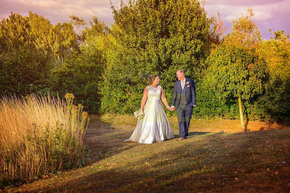 Early evening photo of the Bride and Groom holding hands whilst taking a leisurely stroll in the grounds at the picturesque Marston Forest Centre.