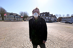 23 March 2020. Montreuil Sur Mer, Pas de Calais, France. <br /> Coronavirus - COVID-19 in Northern France.<br /> <br /> Local resident Frederic Philippe stands in the deserted main square of the ancient citadel town of Montreuil Sur Mer where a statue of Field-Marshal Sir Douglas Haig looks on. Montreuil Sur Mer was the former headquarters of the British Army during WW1. The usually bustling market square is now deserted since From March 16th French lawmakers imposed strict controls on the movement of people in an effort to stem the spread of the virus. Anyone leaving their home must carry with them an 'attestation,' in a effect a self administered permit to allow them out of the house. If stopped by the police, one must produce a valid permit along with identification papers. Failure to do so is punishable with heavy fines. Movement in France has been heavily restricted by the government.<br /> <br /> Montreuil Sur Mer was the headquarters of the British Army under Field-Marshal Sir Douglas Haig from March 1916 to April 1919. Over 1,200 year old, the ancient fortified  town with its high ramparts has endured through history, surviving the plague and King Henry VIII's invasion of France in 1544 when the Duke of Norfolk under Henry VIII's command laid a disastrous siege to the town which held firm until Norfolk was forced to withdraw in 1545. Residents are confident the ancient town can survive the coronavirus too. <br /> Photo©; Charlie Varley/varleypix.com