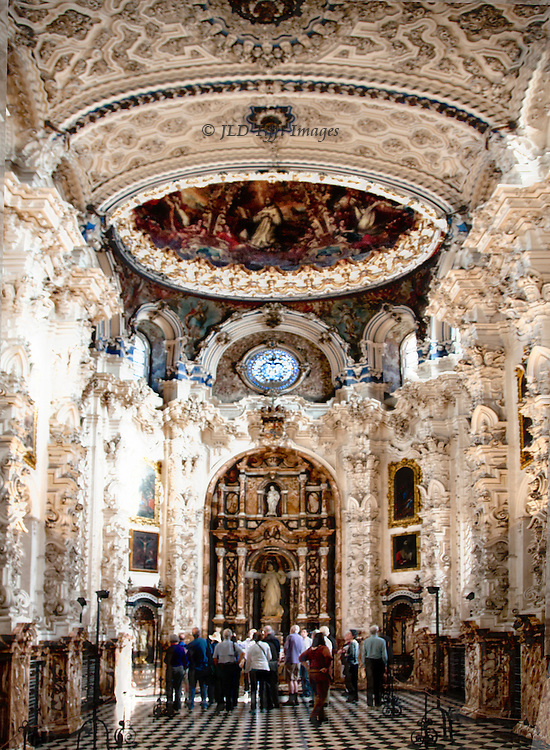 A huddled group of American tourists are dwarfed by the Baroque splendors of the Carthusian monastery church in Granada, Spain.