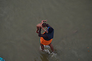 Feb. 8, 2016 - Allahabad, India - <br /> <br /> An indian pilgrim gives a holy dip to his child at holy sangam , on the occasion of ''Mauni Amavasya'' '' or new moon day, in Allahabad, on February 8, 2016. Mauni Amavasya is considered the most auspicious date of bathing during the annual month long ''Magh Mela'' religious fair. ©Exclusivepix Media