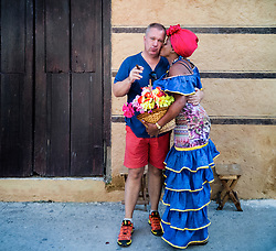 Old Havana, Cuba. Havana vieja, street. Cuban woman in old traditional clothes with tourist.