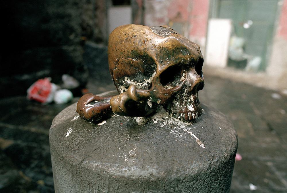ITALIEN - NEAPEL - Alltag.Straflenszene in der Altstadt (Via dei Tribunali).Via del Duomo, Totenkopf in Bronze vor einer Kirche....08.11.2004..©  jungeblodt.com