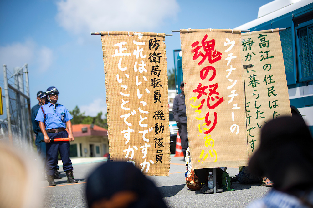 OKINAWA, JAPAN - AUGUST 19 : Anti U.S base protester holding a protest signs to protest against the construction of helipads in front of the main gate of U.S. military's Northern Training Area in the village of Higashi, Okinawa Prefecture, on August 19, 2016. Japanese government resume construction of total six helipads in a fragile ten million year old Yanbaru forest that is home to endemic endangered species such as the Okinawan rail and Okinawa wood pecker. (Photo by Richard Atrero de Guzman/NURPhoto)