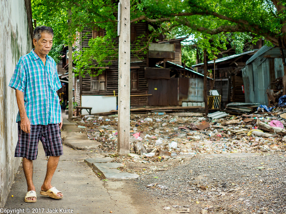 07 JUNE 2017 - BANGKOK, THAILAND:   A man looks at what used to be a neighbor's home in Pom Mahakan. The home was torn down in the first week of June. Bangkok city officials are expected to tear the structure down in coming weeks. The final evictions of the remaining families in Pom Mahakan, a slum community in a 19th century fort in Bangkok, have started. City officials are moving the residents out of the fort. NGOs and historic preservation organizations protested the city's action but city officials did not relent and started evicting the remaining families in early March.         PHOTO BY JACK KURTZ
