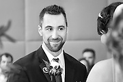 Black and white photo of a groom looking with admiration at his bride during their wedding ceremony at the Turning Stone Resort Casino, Verona, NY