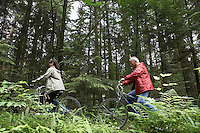Man and woman riding on bicycles in forest side view
