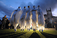 Four visual artists perform in front of Derby Cathedral during Derby Feste. The group walked on stilts and eventually inflated themselves to giant globes.
