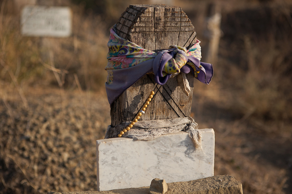 A scarf and a string of beads on a grave in Nokhur village, Turkmenistan