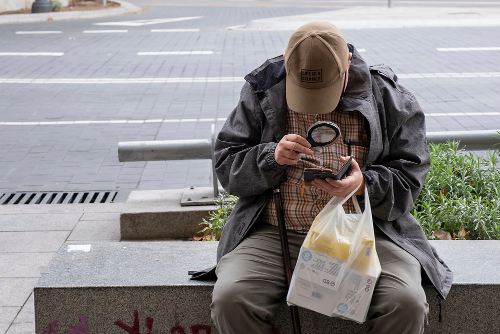 """An elderly man wearing a baseball cap that reads """"Life is a chance"""" using a magnifying glass to read a message on his mobile phone on the 30th of October 2019 whilst sitting on the street outside Atocha train station, Madrid, Spain.  (photo by Andrew Aitchison / In pictures via Getty Images)"""