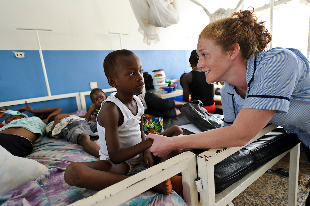Rebecca Cridford with a patient at the Ola During Hospital, Freetown, Sierra Leone. The Welbodi Partnership works to support the Ministry of Health and Sanitation in Sierra Leone to deliver high quality paediatric care.  The work of the charity is designed to stimulate lasting change, whether through one-time investments with long-term benefits, or ongoing engagement around key issues, and the charity's long-term commitment is reflected in its approach to funding - their aim is to establish an endowment fund for the hospitals with which they work..The charity's work is conceived, designed, led and implemented by local partners. Hospital staff in Sierra Leone often already know the best solutions to the numerous problems they face, and where they don't, they are the best judges of new ideas. So the role of the Welbodi Partnership is to coordinate funding, international expertise and local know-how to facilitate improvements in the delivery of health care.  They also work to build relationships and consensus with leaders within the Government of Sierra Leone, local health facilities, donors, NGOs and international partners..Welbodi Partnership works to instil a culture of innovation and excellence with partners and their team of experts. They constantly question the assumptions that underlie their work and the tools that they use, evaluate their efficacy and adapt what they do appropriately.
