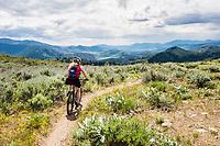 A woman mountain biking on a portion of the Buck Mountain Loop Trail outside Winthrop, Washington, USA.