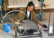 "A woman spins yarn using a bicycle wheel at Jawalakhel Handicraft Center, or ""Little Tibet"", a cooperative workshop in Patan, Nepal, where Nepal's carpet industry was born, at the former Tibetan refugee camp established with help from the Red Cross in 1960."