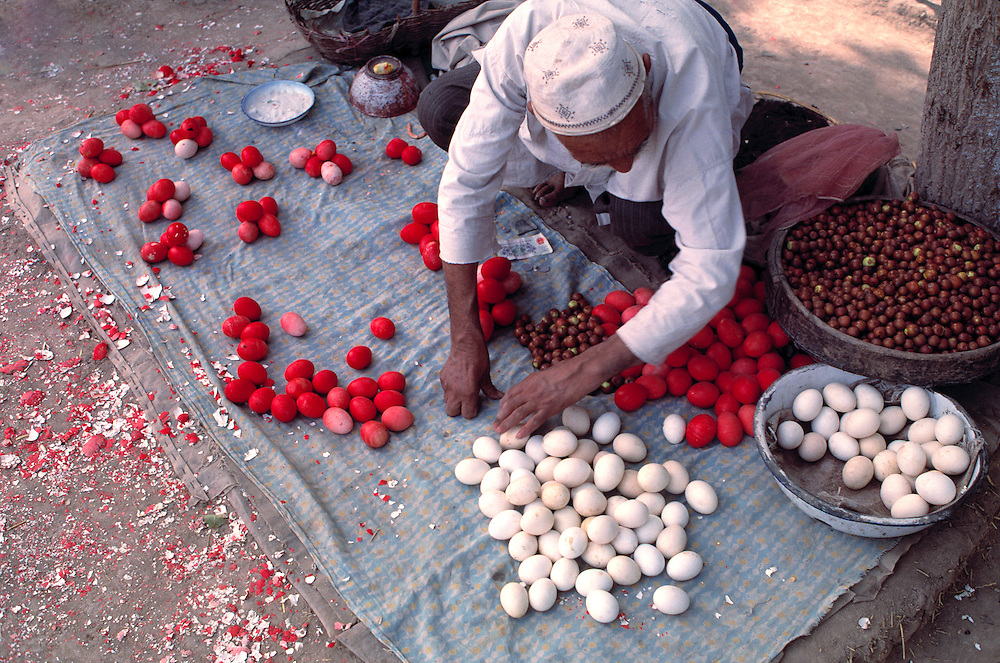An egg seller sorts his red and white eggs on a blue blanket in Kashgar Market, Xinjiang, China.