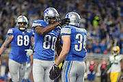 DETROIT, MI - JANUARY 01: Lions running back Zach Zenner (34) is congratulated by Lions wide receiver Anquan Boldin (80) after scoring a touchdown during a NFC North NFL football game between Detroit and Green Bay on January 1, 2017, at Ford Field in Detroit, MI. (Photo by Adam Ruff/Icon Sportswire)