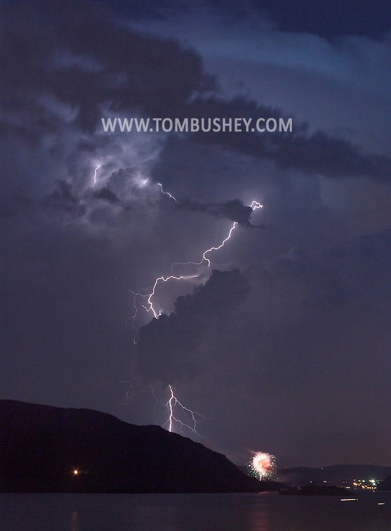 Newburgh, New York - Lightning illuminates the sky above the Hudson River as a fireworks display goes on in a view looking south on July 4, 2012.