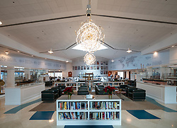 Interior of Queen Elizabeth 2 hotel reception area with library stocked with books from the original cruise liner in Dubai, United Arab Emirates.