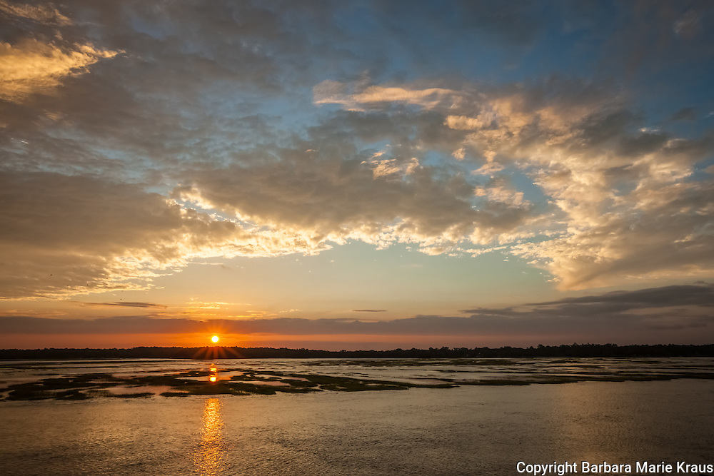 The sunsets over the Sapelo River during a very high tide.