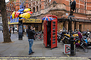 Tourists pose a picture in a red phone box outside the Palace Theatre where the musical Singing in the Rain is playing.