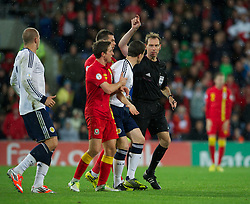 CARDIFF, WALES - Friday, October 12, 2012: Scotland's Gary Caldwell argues with referee Florian Meyer during the Brazil 2014 FIFA World Cup Qualifying Group A match against Wales at the Cardiff City Stadium. (Pic by David Rawcliffe/Propaganda)