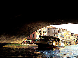 Venice, Italy: A loaded vaporetto (waterbus) passes beneath the Rialto Bridge on the Grand Canal.