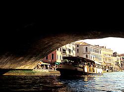 Venice, Italy: A loaded vaporetto (waterbus) passes beneath the Rialto Bridge on the Grand Canal.