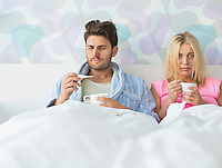 Sad couple holding coffee mugs while relaxing on bed