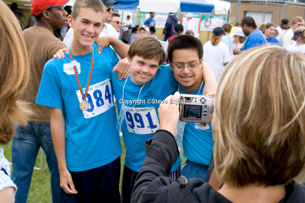 Athletes posing at award ceremony for mom's camera. Special Olympics U of M Bierman Athletic Complex. Minneapolis Minnesota USA