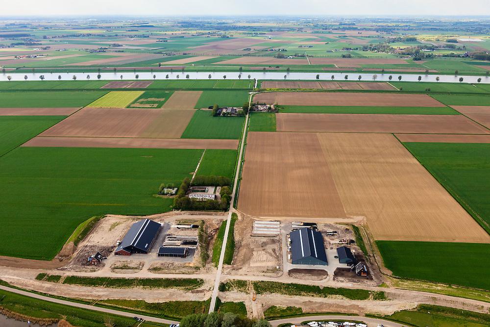 Nederland, Brabant, Gemeente Waspik, 09-05-2013; Overdiepsche polder: in het kader van het programma 'Ruimte voor de Rivier' (bescherming tegen hoogwater door rivierverruiming), zal de dijk langs de Bergsche Maas (boven in beeld) verlaagd worden. Bij hoogwater kan de Overdiepse polder overstromen. De boerderijen in de polder worden gesloopt en verplaatst naar de dijk van het Oude Maasje. De nieuwe boerderijen met bijgebouwen komen op terpen.<br /> Depoldering of Overdiep Polder, farms are relocated and built on mounds. This makes it possible for the river to overflow the polder in case of heigh waters.<br /> luchtfoto (toeslag op standard tarieven);<br /> aerial photo (additional fee required);<br /> copyright foto/photo Siebe Swart.