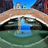 Ponte Nuovo Bridge Reflecting in Canal Water in Venice, Italy <br /> The Castello District on the eastern side of Venice is a charming and unrushed local neighborhood.  This red brick Ponte Nuovo bridge reflecting in the waters of the Rio de la Tan canal is typical of its enchanting features.