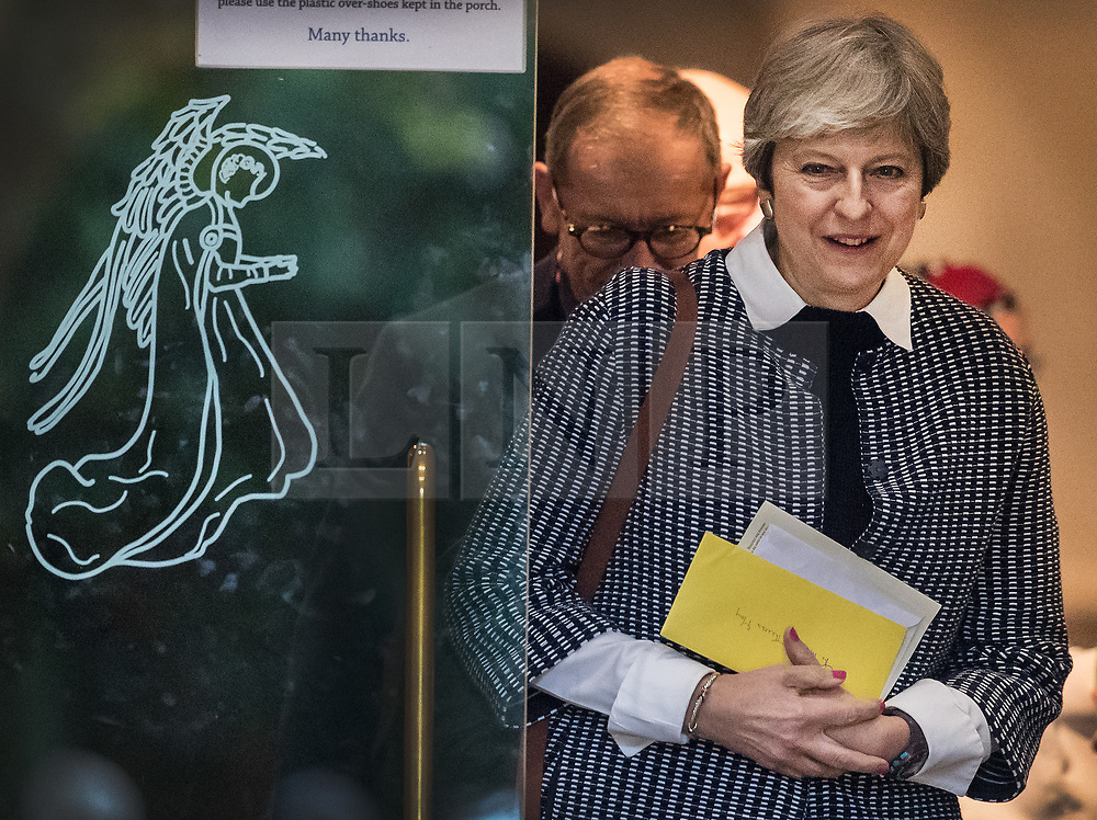 © Licensed to London News Pictures. 08/10/2017. Maidenhead, UK. Prime Minister Theresa May and her husband Philip pass a door decorated with an image of an angle as they attend church in her constituency. Mrs May has faced heavy criticism after her disastrous conference speech, with some MPs in the Conservative party calling for her to stand down.  Photo credit: Peter Macdiarmid/LNP