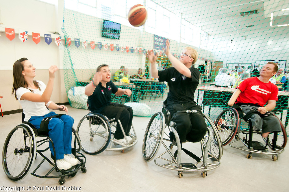 Cadbury 2012 Paralympic demonstration Sheffield..Kraft Lab scientist Kayleigh Jones tries her hand at wheelchair basketball alongside coach Andy Atkinson (far right) and players Josh Dunn and Mike Porter who were on site with the  RGK Rhinos Sporting club wheelchair basketball team to give Sheffield colleagues an insight into Wheelchair basketball, Paralympic sports and promote awareness around the different sporting disciplines.   .  ....3 September 2012.Image © Paul David Drabble