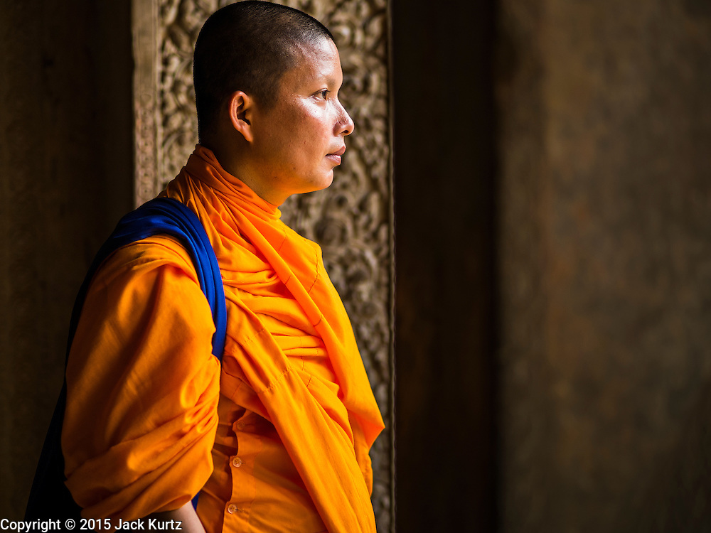 "13 MARCH 2015 - SIEM REAP, SIEM REAP, CAMBODIA: A Buddhist monk walks through Angkor Wat. The area known as ""Angkor Wat"" is a sprawling collection of archeological ruins and temples. The area was developed by ancient Khmer (Cambodian) Kings starting as early as 1150 CE and renovated and expanded around 1180CE by Jayavarman VII. Angkor Wat is now considered the seventh wonder of the world and is Cambodia's most important tourist attraction.   PHOTO BY JACK KURTZ"