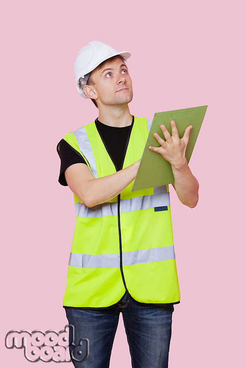 Male construction worker with clipboard looking away over pink background