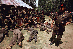 July 1997. Srinagar, Kashmir, India..Members of the Indian Army's elite 'Victor Force' show off the corpses of 7 dead militants killed in a fire fight high in the Pir Panjal mountains separating India from Pakistan. 3 militants were Pakistani, 3 Afghan and only one Kashmiri. .Photo; Charlie Varley