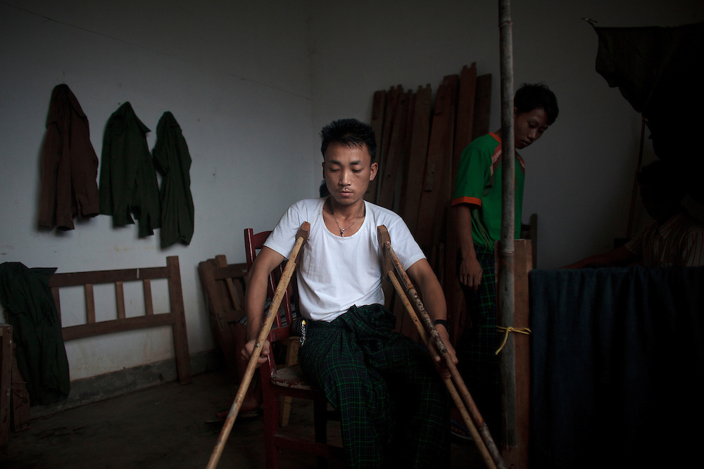 Kachin's militia member Lalaw Ze Dai, from Waimaw village, 25, try to stand up with his crutches in the General Military Hospital in Laiza village close to the China border, Myanmar on July 26, 2012. He was injured by a landmine in June, 26, 2012 loosing part of his right leg on top of knee.